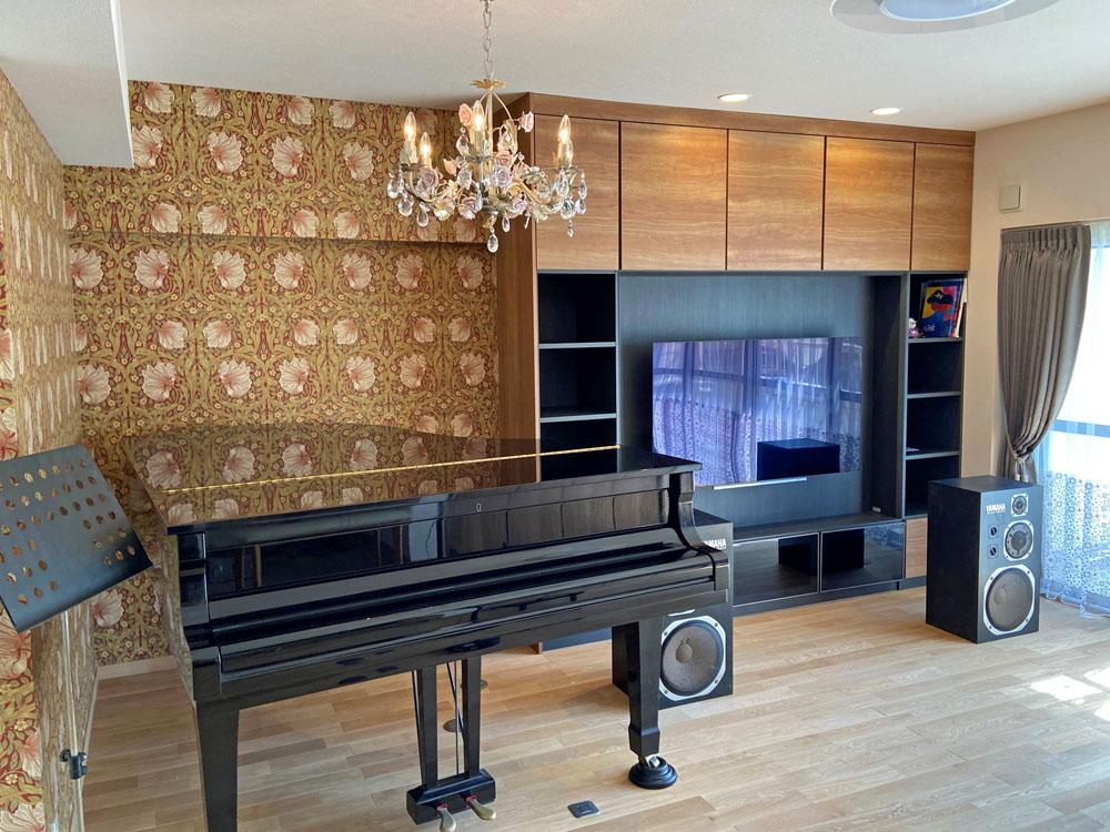 ウィリアム・モリスの壁紙を使用したグランドピアノのあるコーナー