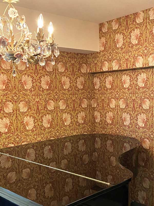 グランドピアノのトップにウィリアム・モリスの壁紙ピンパネルが映り込む様子